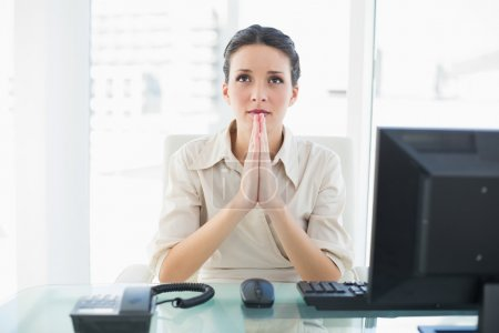 Photo for Troubled stylish brunette businesswoman praying in bright office - Royalty Free Image