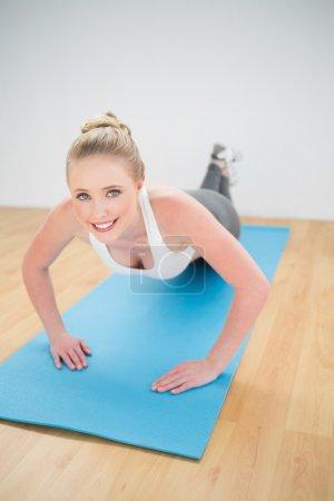 Smiling sporty blonde doing push ups