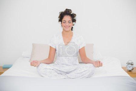 Smiling natural brunette sitting in lotus pose