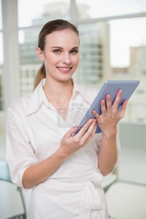 Happy businesswoman holding her tablet pc