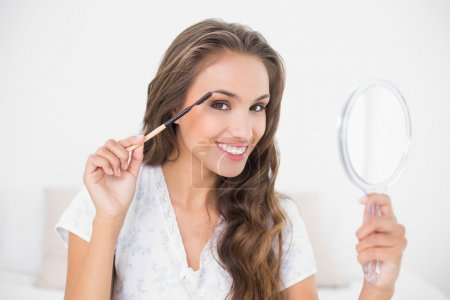 Brunette using eyebrow brush and mirror
