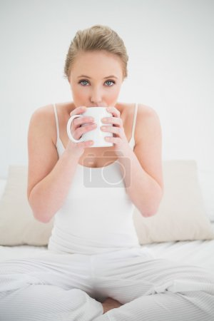 Natural pretty blonde drinking from a mug