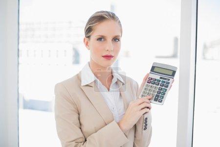 Photo pour Femme d'affaires blonde sérieuse dans un bureau lumineux montrant calculatrice - image libre de droit