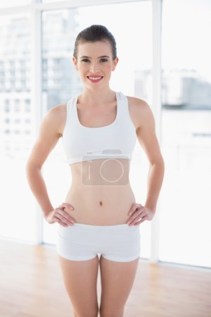 Pleased fit model in sportswear posing with hands on the hips