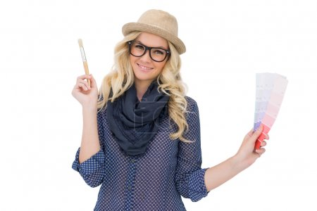 Cheerful trendy blonde with classy glasses holding color chart