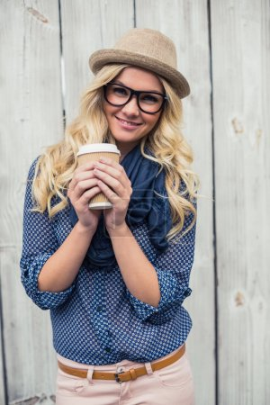 Happy trendy blonde holding coffee outdoors