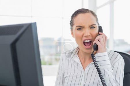 Angry businesswoman screaming on telephone