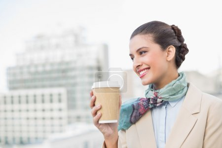 Happy businesswoman holding a cup of coffee