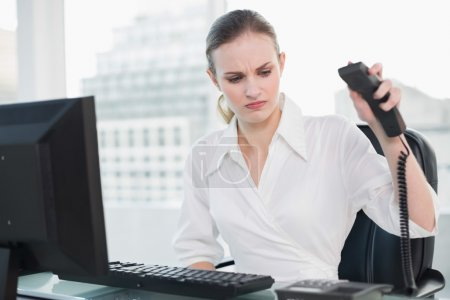 Angry businesswoman sitting at desk hanging up phone