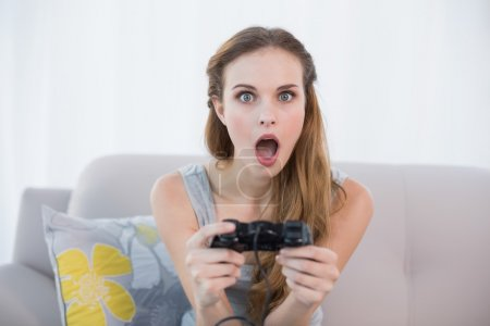 Shocked young woman sitting on sofa playing video games