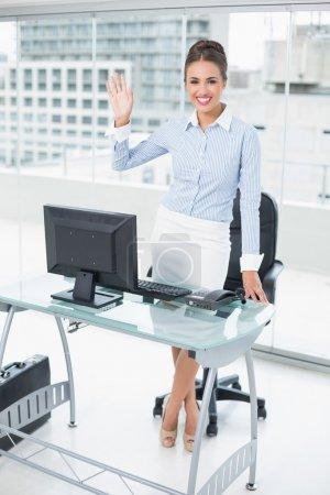 Photo pour Souriante femme d'affaires brune saluant dans un bureau lumineux - image libre de droit