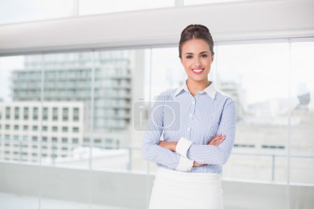 Smiling brunette businesswoman standing with arms crossed