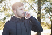 Vážný muž venku pomocí mobilního telefonu