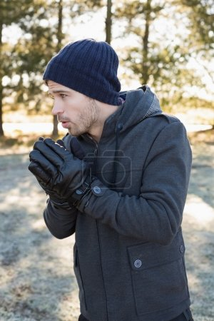 Man in warm clothing shivering while having a walk in forest