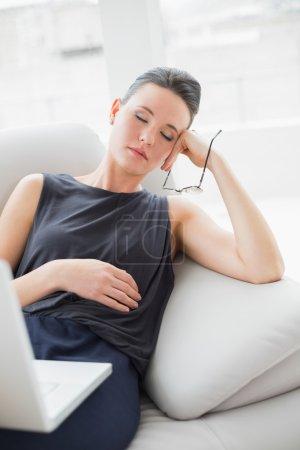 Foto de Hermosa mujer joven bien vestida descansando en el sofá mientras usa el ordenador portátil en casa - Imagen libre de derechos