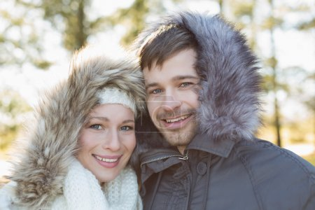 Close-up portrait of a smiling young couple in fur...