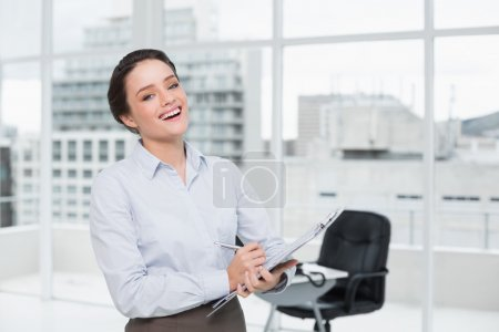 Cheerful elegant businesswoman with clipboard in office