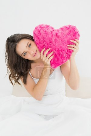 Cute woman holding heart shaped pillow in bed
