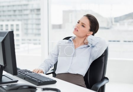 Photo for Young businesswoman with neck pain sitting at office desk - Royalty Free Image