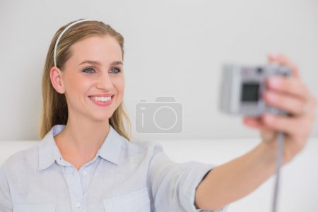 Smiling casual blonde sitting on couch taking a picture of herse