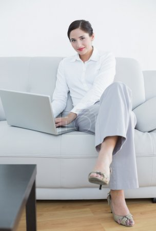 Portrait of a well dressed woman using laptop on sofa