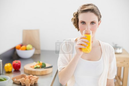 Gorgeous woman drinking a glass of orange juice standing