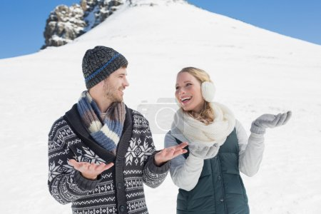 Couple with hands open looking at each other in front of snowed
