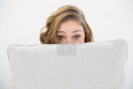 Astonished brunette woman hiding her face behind a white pillow
