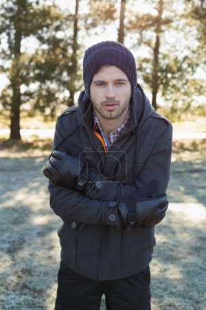Foto de Young man in warm clothing shivering while having a walk in forest on a winter day - Imagen libre de derechos