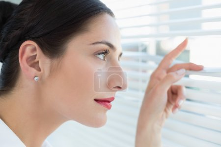 Young business woman peeking through blinds at office