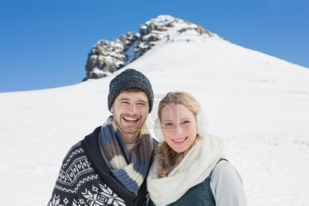 Couple in front of snowed hill and clear blue sky