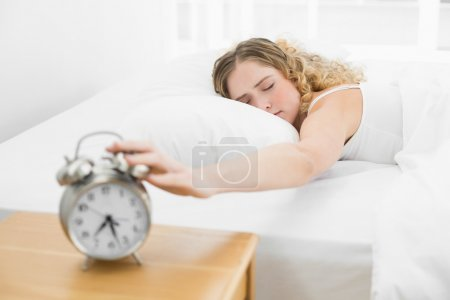 Pretty tired blonde lying in bed turning off alarm clock