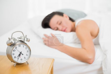 Blurred woman sleeping in bed with alarm clock on bedside table