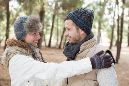 Photo pour Joyeux jeune couple en vêtements d'hiver se regardant dans les bois - image libre de droit