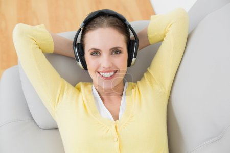 Photo for Smiling young woman lying on sofa and listening music through headphones - Royalty Free Image