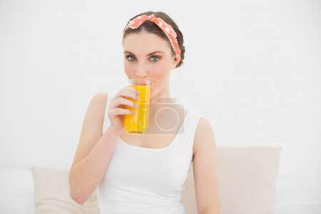 Woman drinking a glass of orange juice looking into the camera