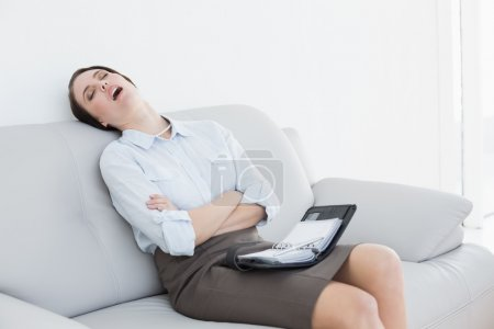 Tired well dressed woman sitting and sleeping on sofa