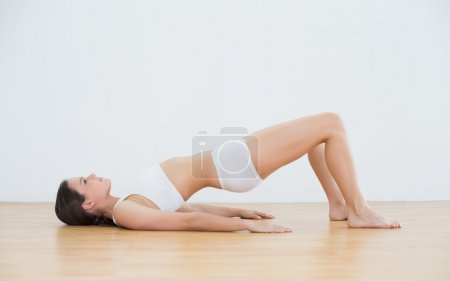 Woman doing the bridge pose in fitness studio