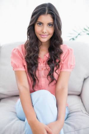 Content cute brunette sitting on couch looking at camera