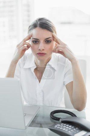 Businesswoman having a headache at work