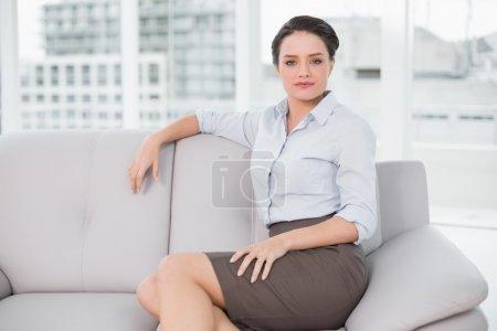 ernst gut gekleidete junge Frau sitzt zu Hause auf Sofa