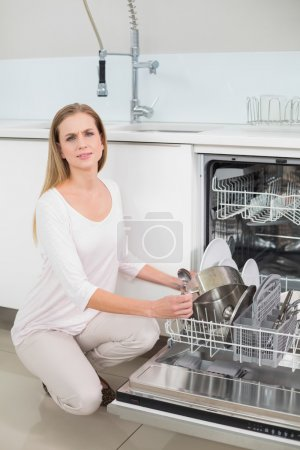 Frowning gorgeous model kneeling next to dish washer