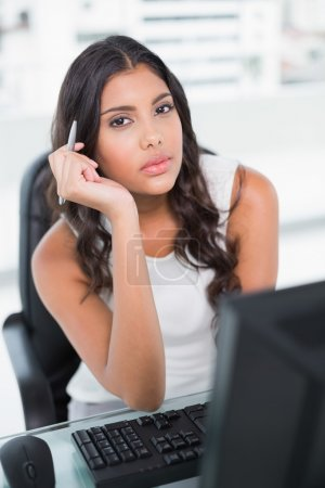 Thoughtful cute businesswoman holding pen looking at camera