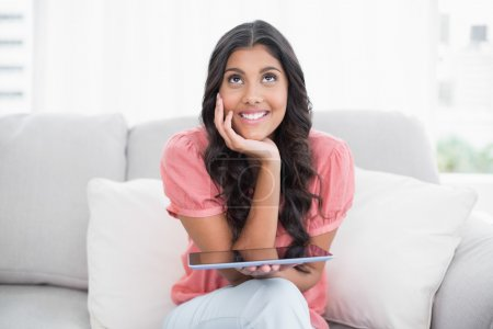 Day dreaming cute brunette sitting on couch holding tablet