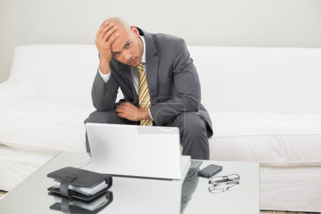 Photo for Portrait of a worried young businessman with laptop and diary holding head in hand at home - Royalty Free Image