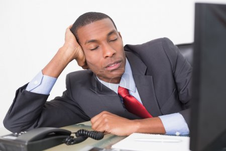 Young Afro businessman resting at desk against whi...
