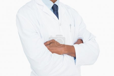 Close up mid section of a male doctor with arms crossed