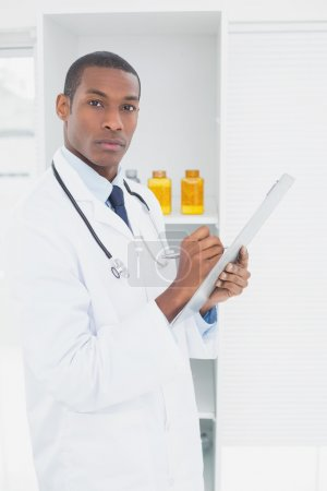 Photo for Portrait of a serious male doctor writing a prescription in medical office - Royalty Free Image