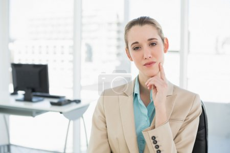 Thoughtful calm businesswoman sitting on her swivel chair