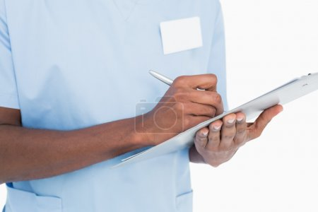 Mid section of a male surgeon writing on clipboard